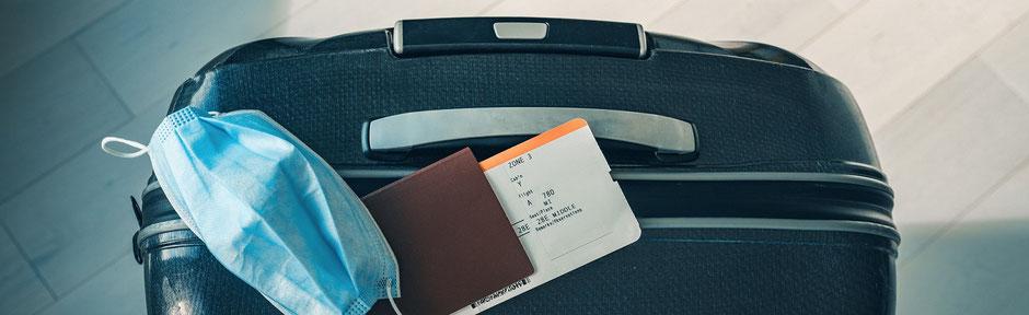 Gepackter Urlaubskoffer mit Pass, Flugticket, Impfausweis, OP-Maske und Corona-Zusatz-Reiseschutz Covid-19 der ERGO Reiseversicherung
