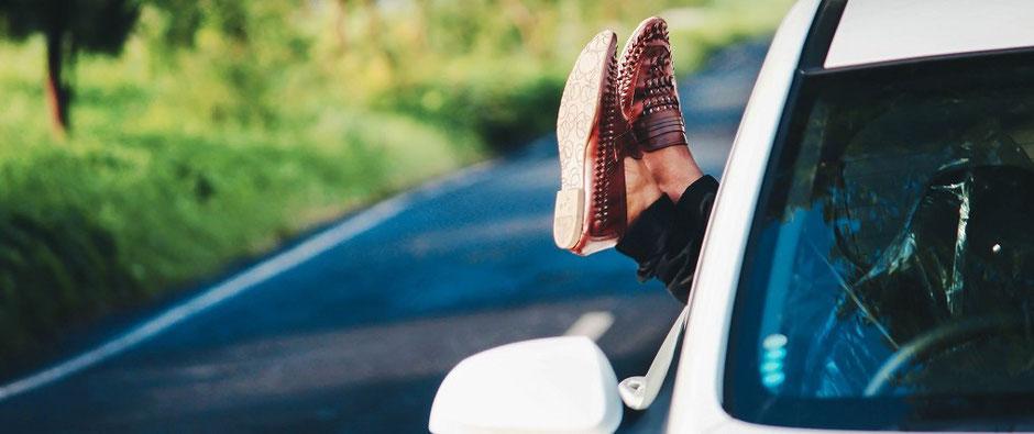 Mit den Füßen aus dem Fenster eines Autos entspannt in den Urlaub reisen