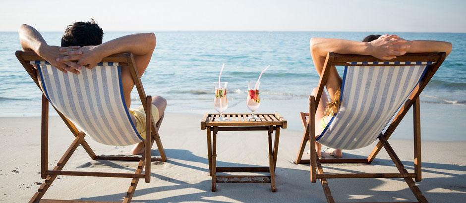 Zwei Menschen liegen im Liegestuhl mit Cocktails am Meer gut versichert mit der ERGO-Jahres-Reiseversicherung für alle Reisen und Urlaub mit Pandemie-Corona-Reiseschutz