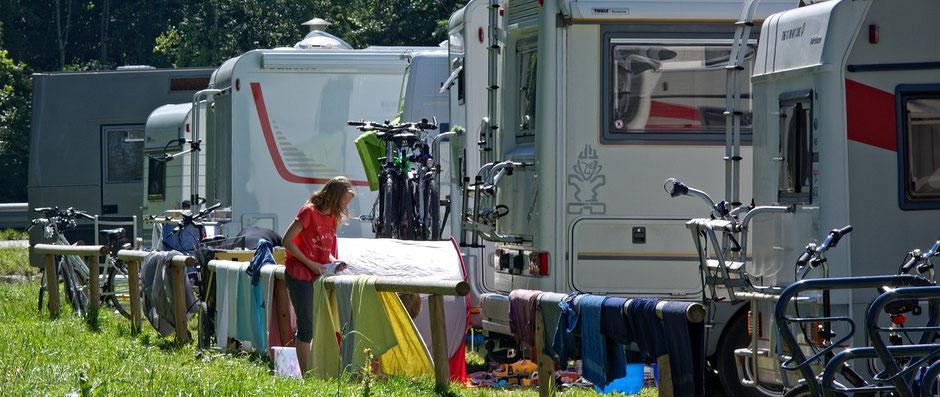 Frau hängt Wäsche auf vor ihrem Wohnmobil. Im Hintergrund auf dem Campingplatz sieht man mehrere Wohnwagen.