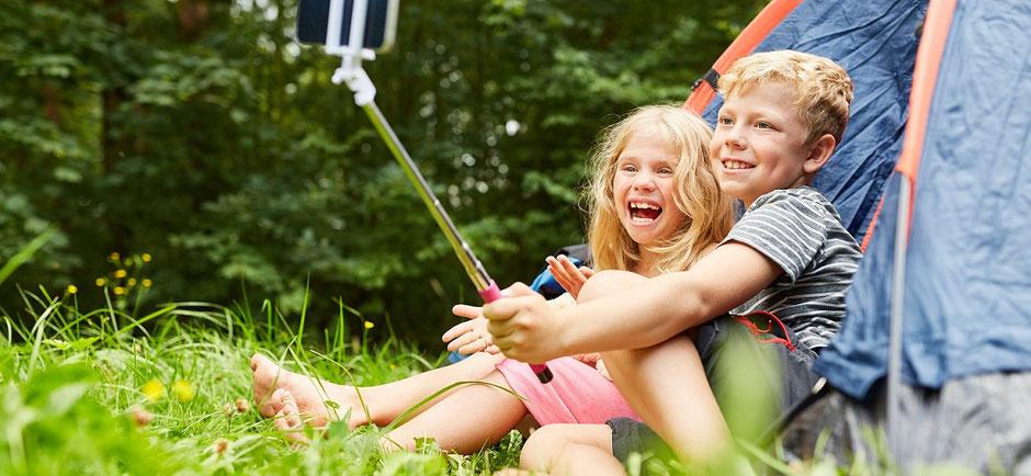 Ein Junge und ein Mädchen machen Selfies auf dem Campingplatz und lachen. Die Eltern haben eine Camping-Reiseversicherung der ERGO mit Camping-Reiseschutz für Deutschland.