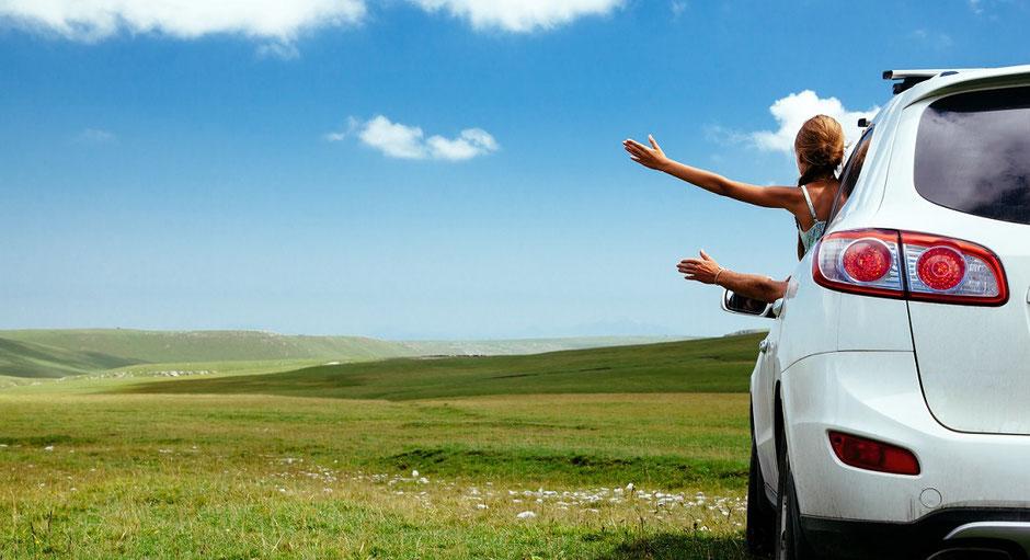 Ein weißes Auto auf einer grünen Wiese vor blauem Himmel im Deutschlandtourismus, aus dem ein Mädchen seine Hand streckt. Hoffentlich gut geschützt mit einer Reiseversicherung und Coronapandemie-Ergänzungsschutz Covid-19