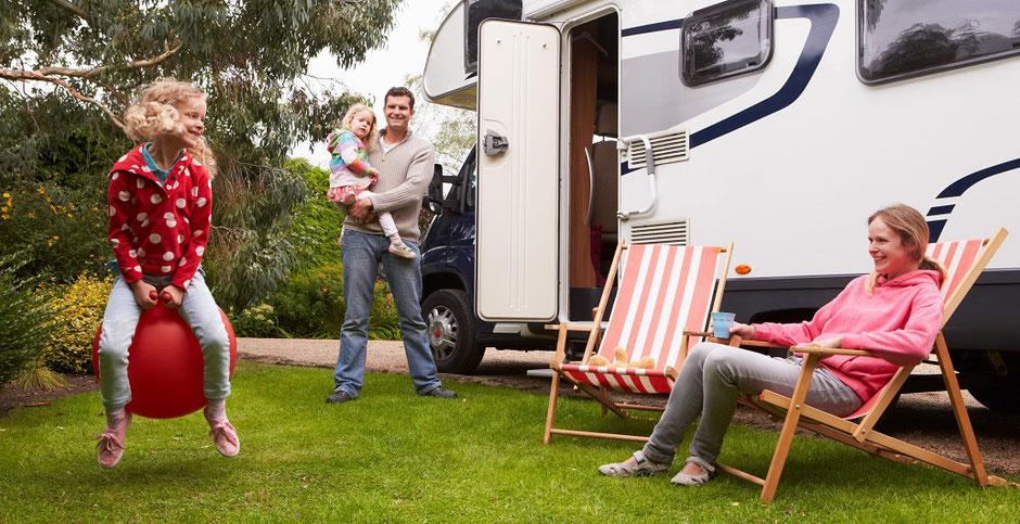 Eine Familie vor ihrem Wohnmobil auf einem Campingplatz. Gut geschützt mit einer Camping-Reiseversicherung der ERGO.