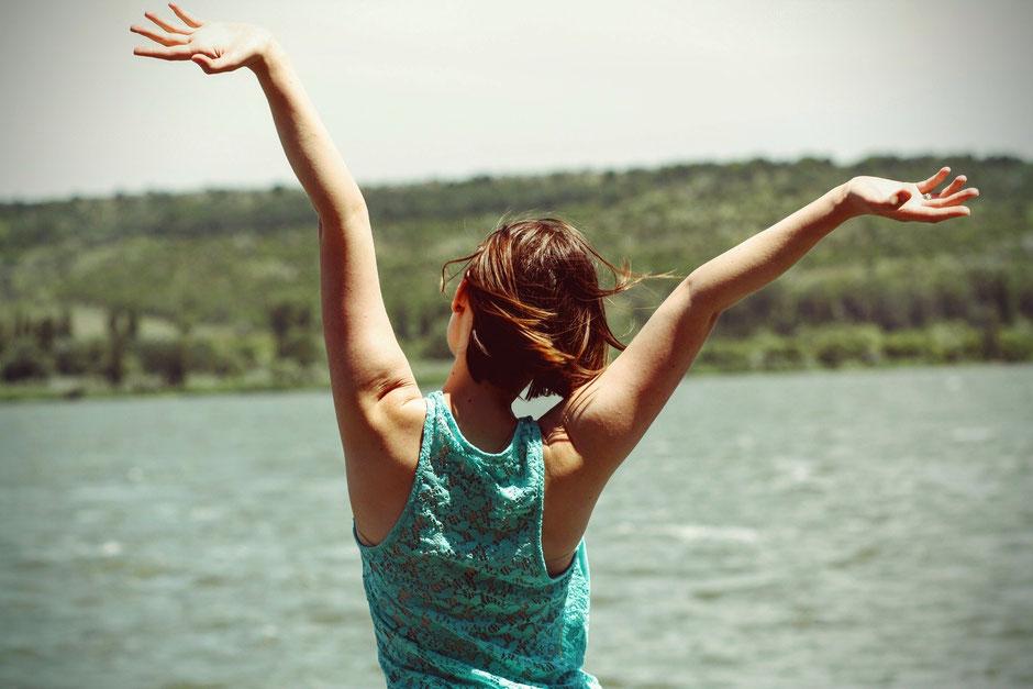 Frau, die die Arm ausstreckt und sich frei fühlt