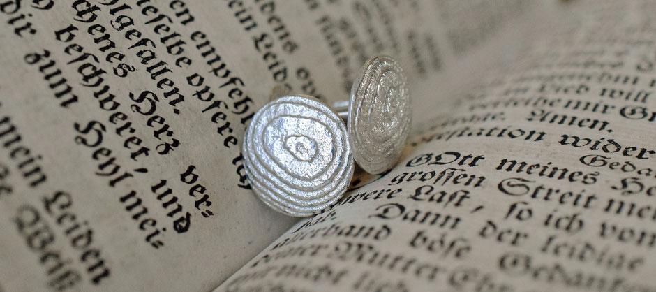 Bild: Manschettenknöpfe aus Silber in einem Buch