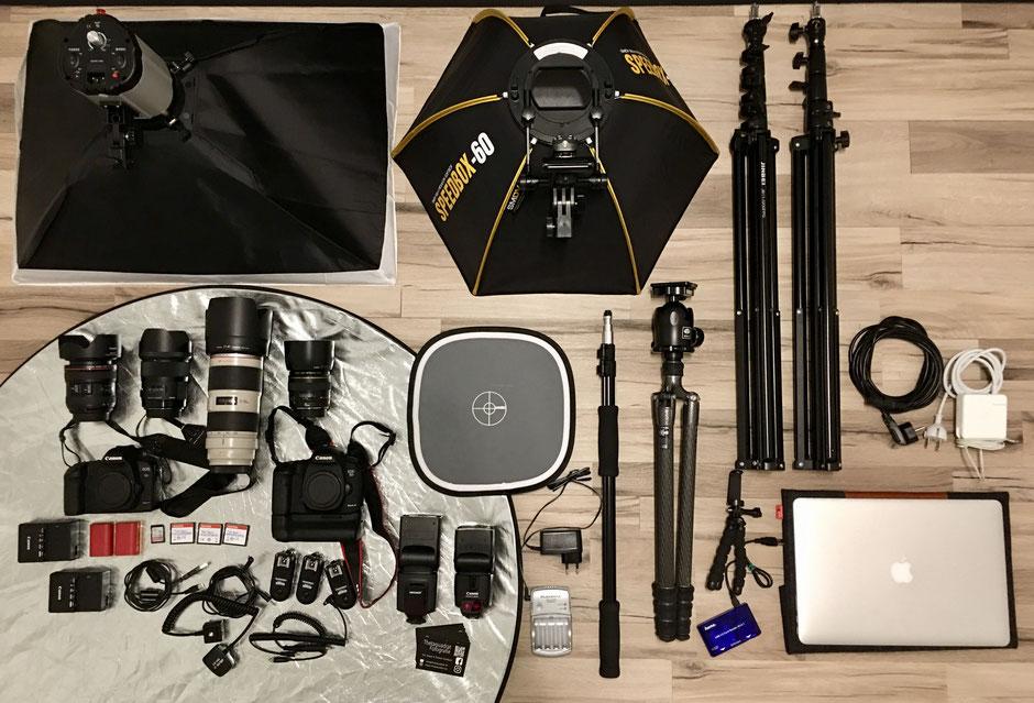 Mein Equipment von links nach rechts: Stationäre Softbox, Reflektor, zwei Kameras, div. Objektive, Speicherkarten, Akkus, Funkauslöser, Systemblitze, Graukarte, Mobile Softbox, Stative, Laptop.
