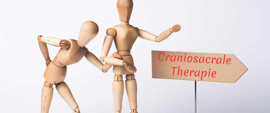 Auf dem Foto ist eine Person mit Rückenschmerzen zu sehen, die von einer anderen Person gestützt wird. Auf dem Schild dazu steht craniosacrale Therapie.