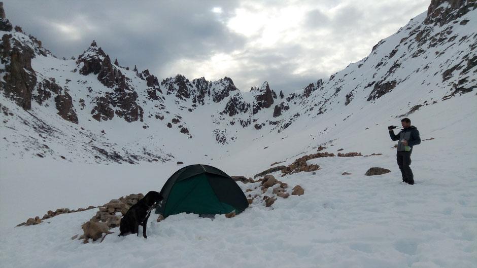 Notre tente dans la neige au pied des montagnes avec Filo qui pose devant