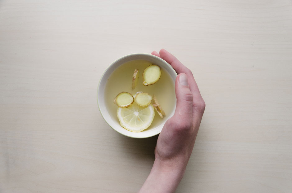hand with a cup of ginger lemon tea