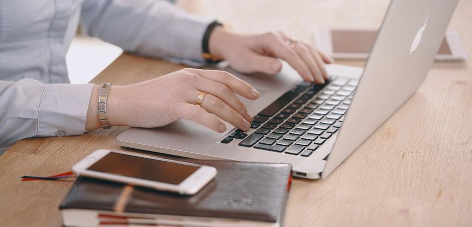 Frauenhände buchen am Laptop die Seminar-Versicherung der ERGO Reiseversicherung, ein Handy liegt auf dem Tisch. Zusätzlich mit Corona-Quarantäne-Schutz-Absicherung.