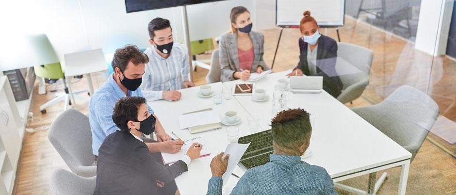 Menschen sitzen während eines Seminars am Tisch, tragen alle Masken als Corona-Seminar-Reiseschutz. Der neue Covid-19-Ergänzungs-Schutz zahlt bei Quarantäne die Seminar-Stornokosten.