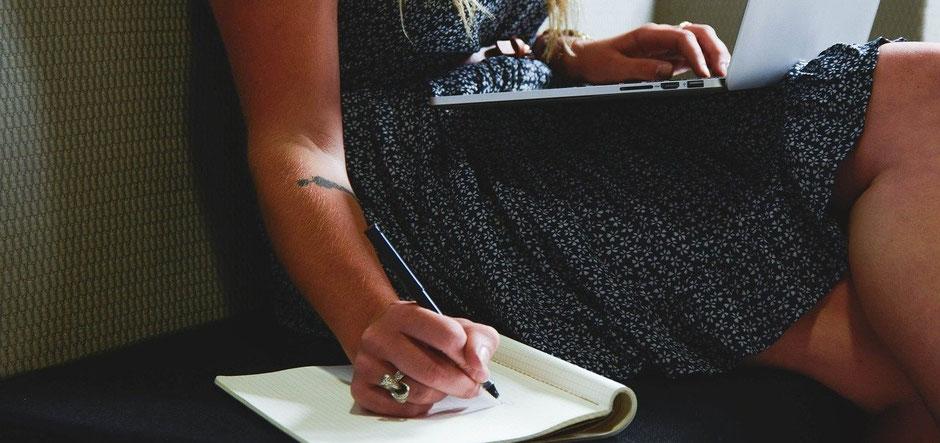 Frau mit Laptop auf Knie und Stift und Zettel in der Hand beim Umbuchen einer Seminarversicherung