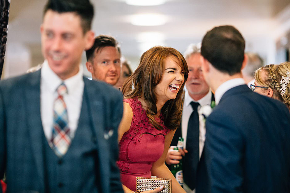 candid photograph of a wedding guest laughing