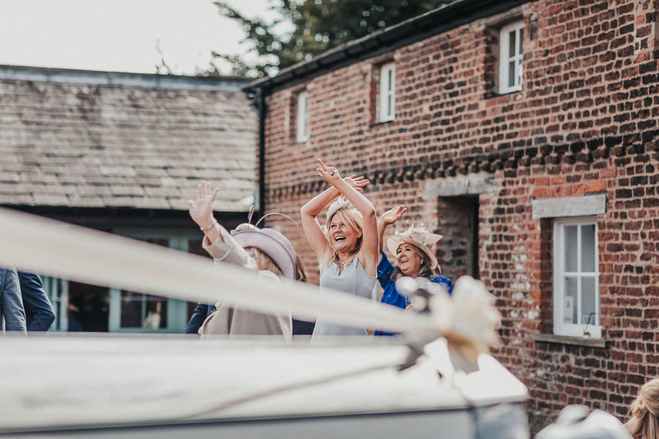 candid shots of guests at meols hall waving at a drone