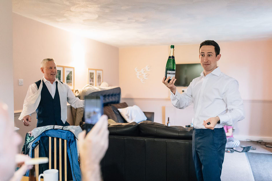 a photograph of a man holding up a bottle of champagne