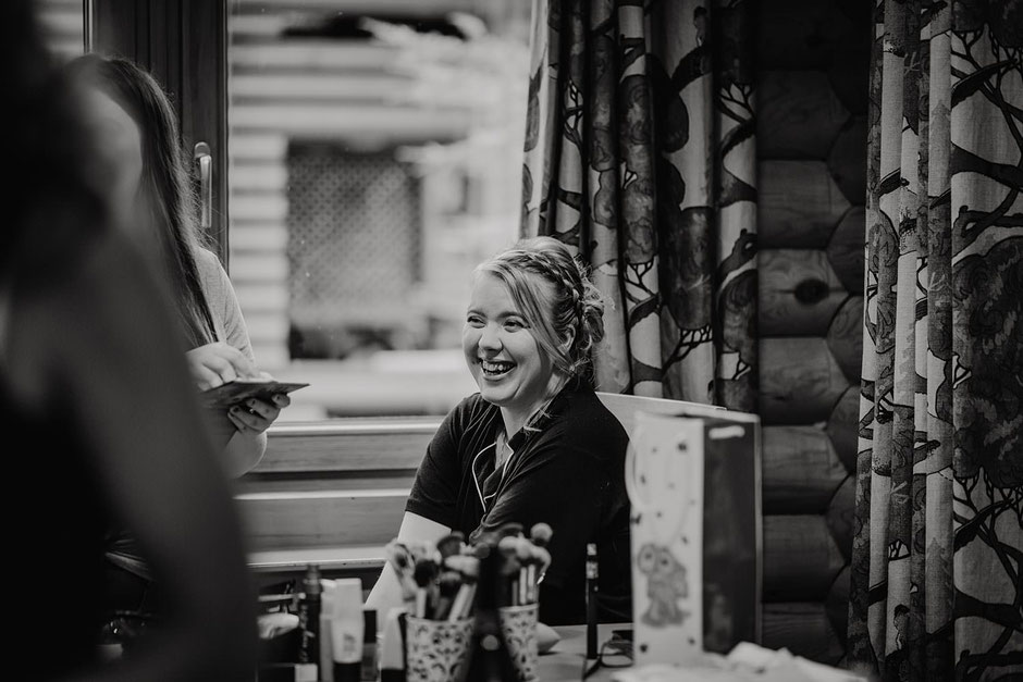 black and white photograph of a bride laughing as she has her make up done