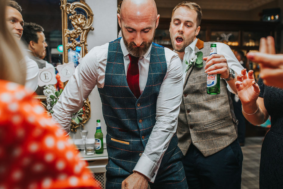a man in a tweed suit doing the floss dance at a wedding reception