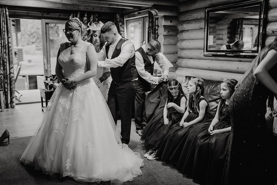 black and white photo of a bride being fastened into her dress whilst three flower girls look on