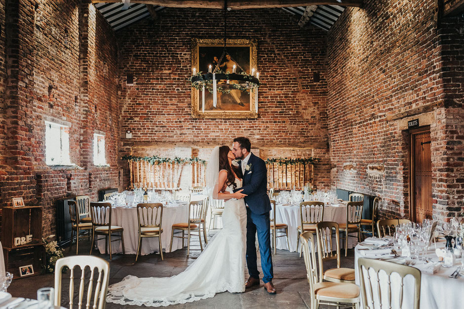 a bride and groom kissing in the barn at meols hall surrounded by their set up tables