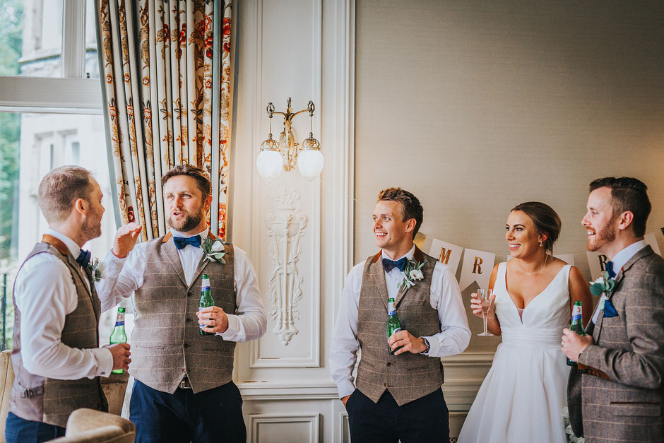 candid photograph of wedding guests holding beers and chatting