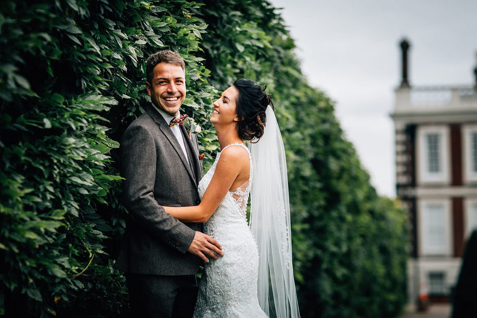 portrait of a bride and groom resting on a bush in the gardens of knowsley hall