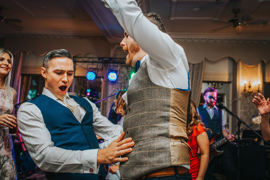 two men dancing at a wedding dressed in waistcoats