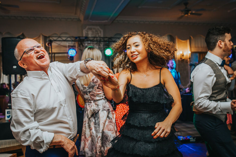 man and lady dancing at a wedding whilst holding hands