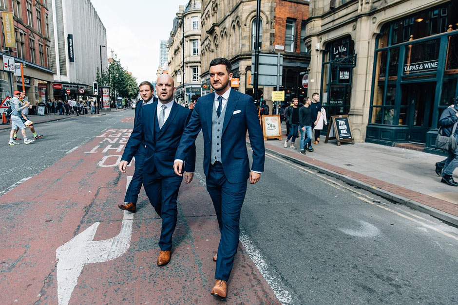a groom and his best man walking to his wedding dressed in a blue suit in the city of manchester