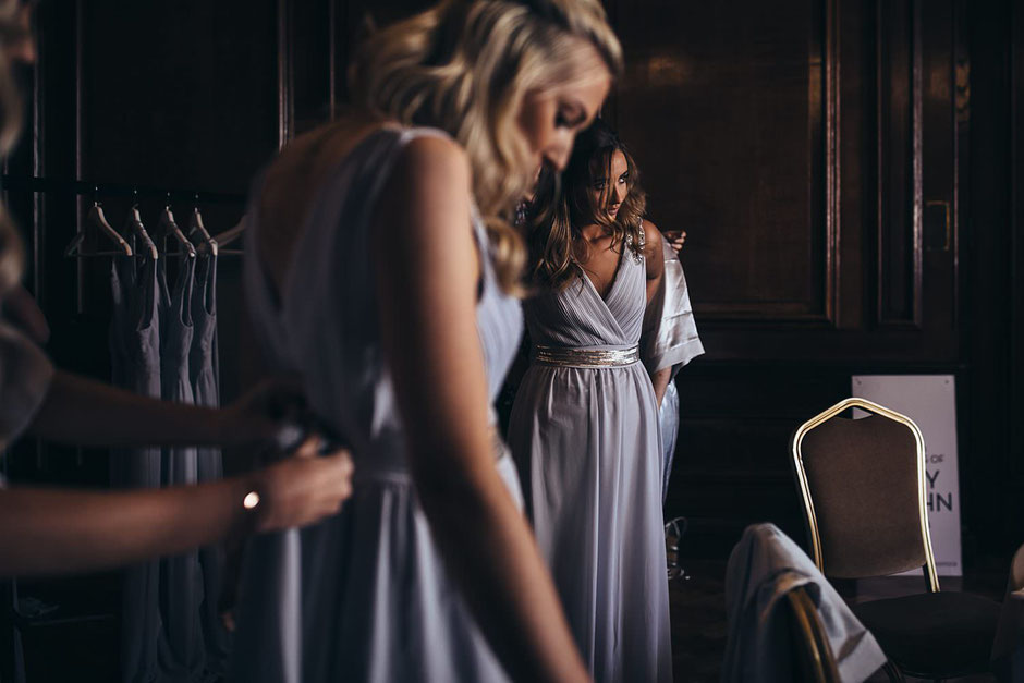 two bridesmaids putting their dresses on