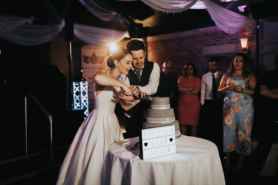 bride and groom cutting their grey wedding cake