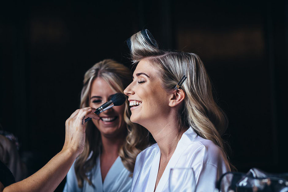 a bride having her make up done before her wedding and laughing