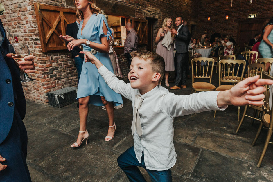 a little boy having fun with his arms out wide dancing to music