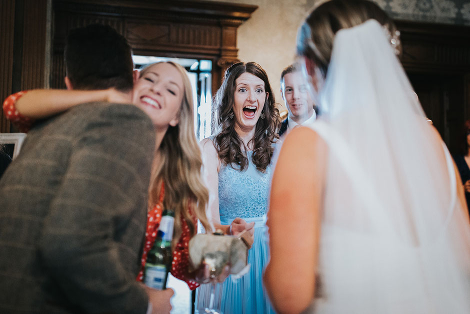candid photo of a wedding guest dressed in a blue dress excited to see the bride