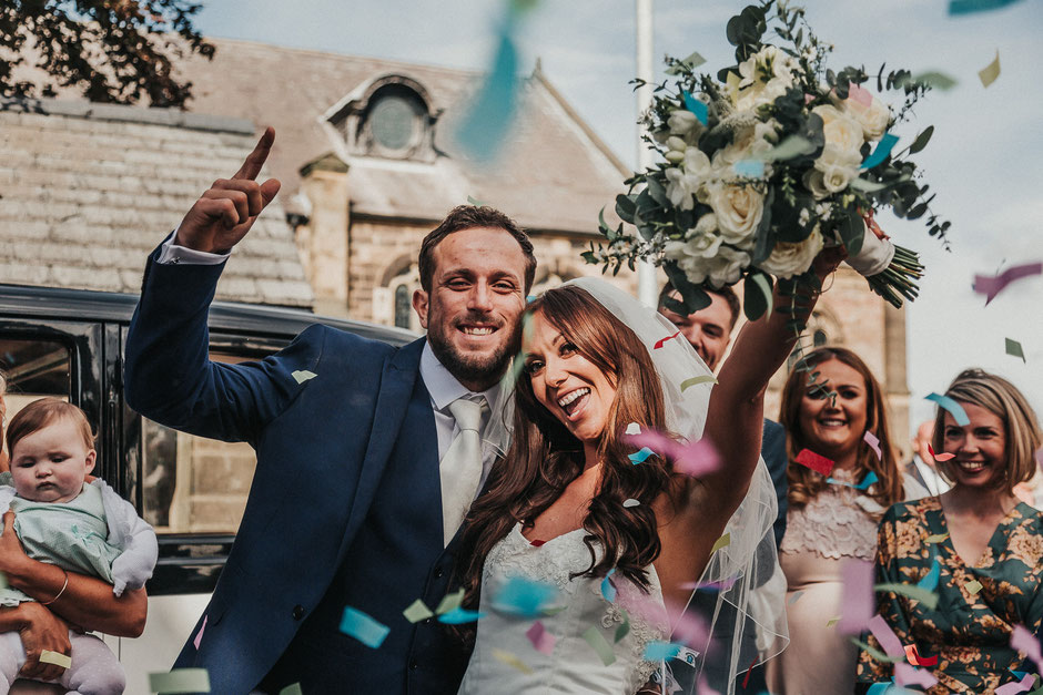 bride and groom cheering outside church with confetti flying everywhere