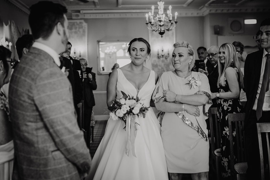 black and white photograph of a bride walking towards her soon to be husband with tears in her eyes