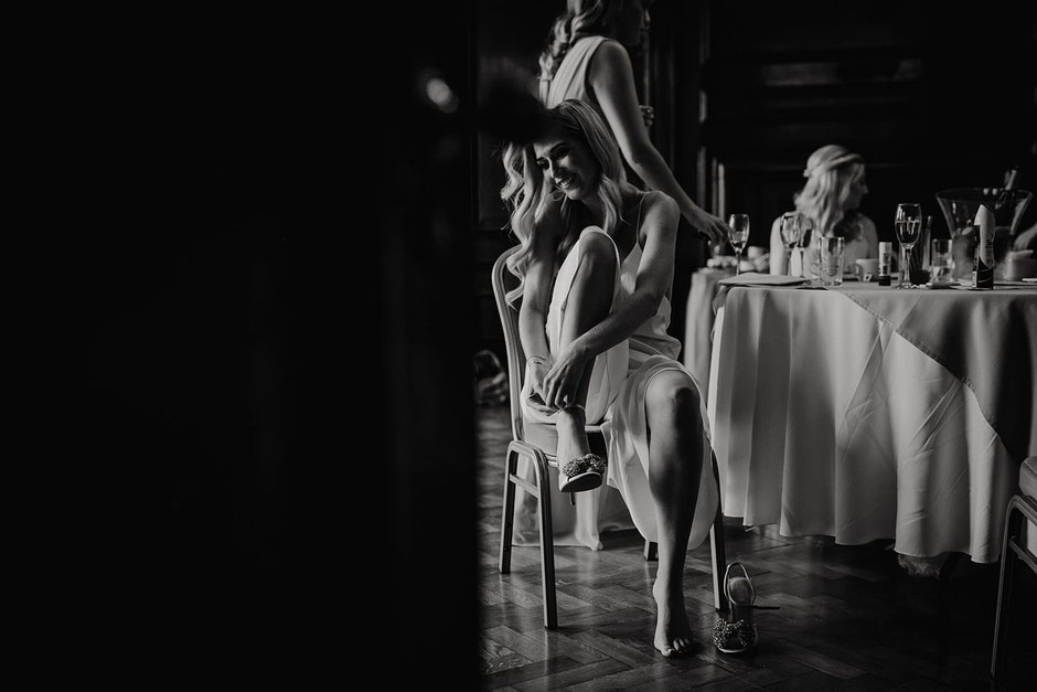 black and white photograph of a bride sat on a chair putting her shoes on