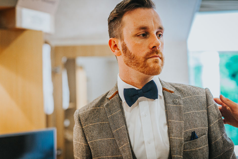 Groom in a tweed suit and bow tie on the morning of his Lake District wedding
