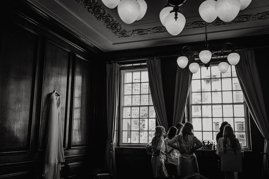 a wedding dress is hanging on the wall inside Manchester hall & a group of girls are stood around a table near a window