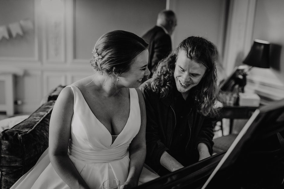 bride sat with her brother at a piano whilst he plays her a song