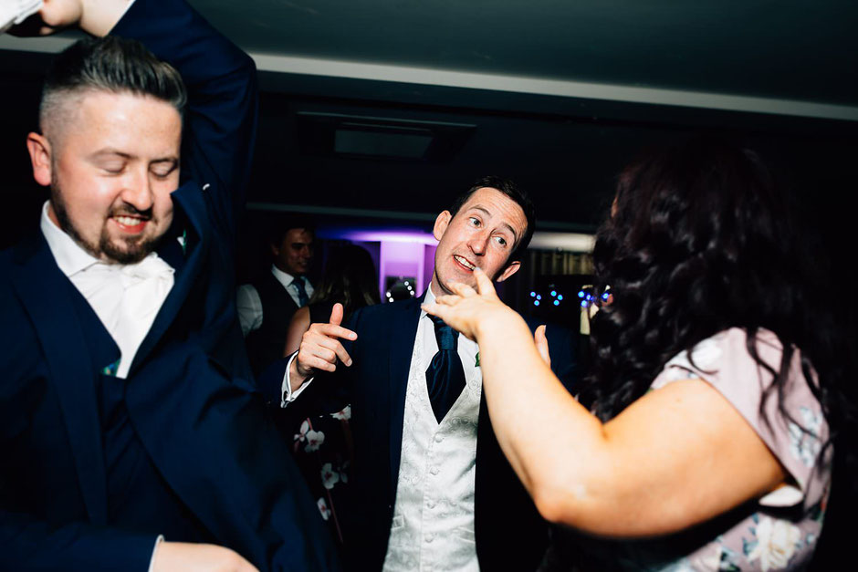 wedding guests on a dancefloor singing