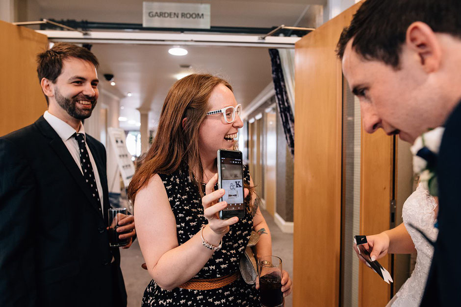 candid photograph of wedding guests laughing at a picture on a phone