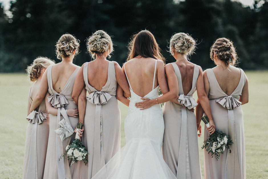 a photograph of a bride and her bridesmaids showing the details on the backs of their dresses
