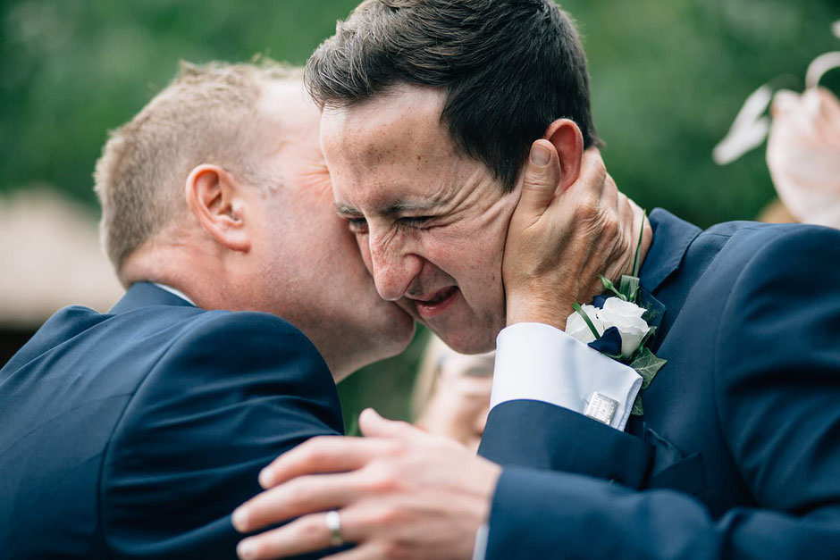 photograph of a groom being kissed my his new father in law and pulling a face