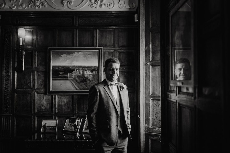 black and white portrait of a groom in a tweed suit lit with window light