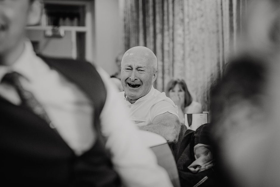 black and white photograph of a man laughing during wedding speeches at Ribby hall