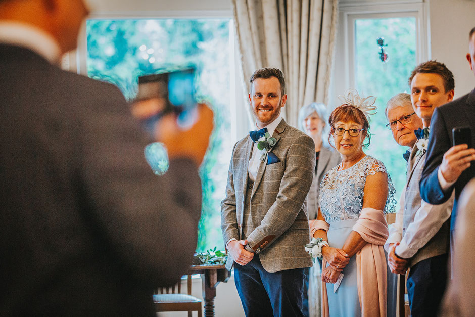 Groom and his mother turned to look up the aisle as his soon to be bride walks to meet him