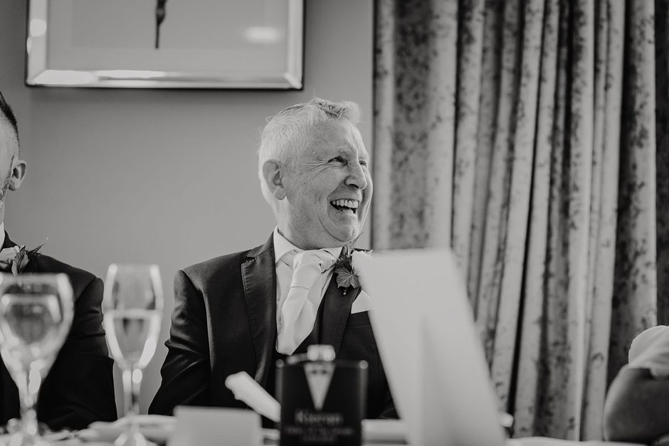 black and white photograph of a man laughing during wedding speeches