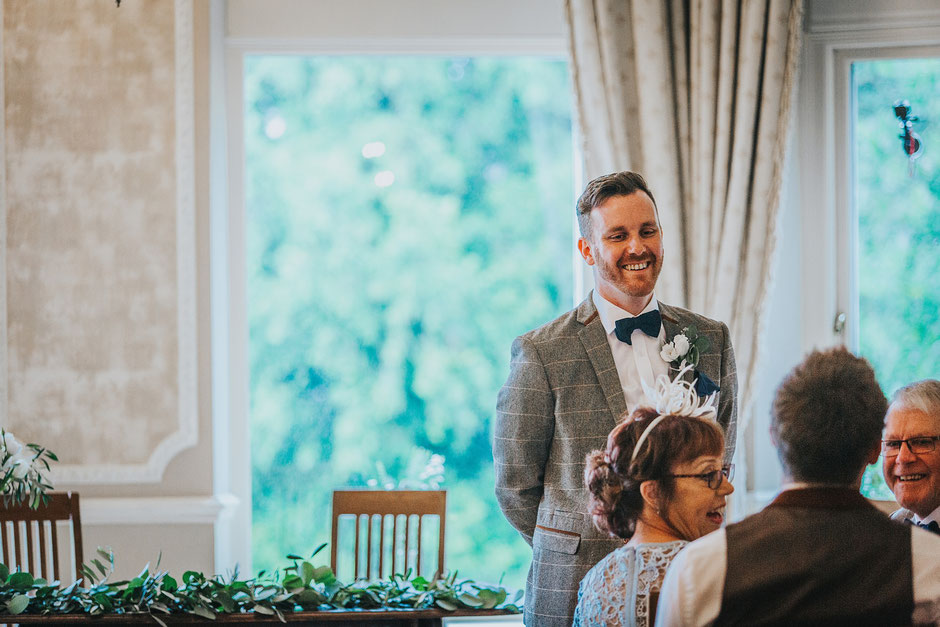 A candid photograph of a groom standing in the ceremony room waiting for his bride