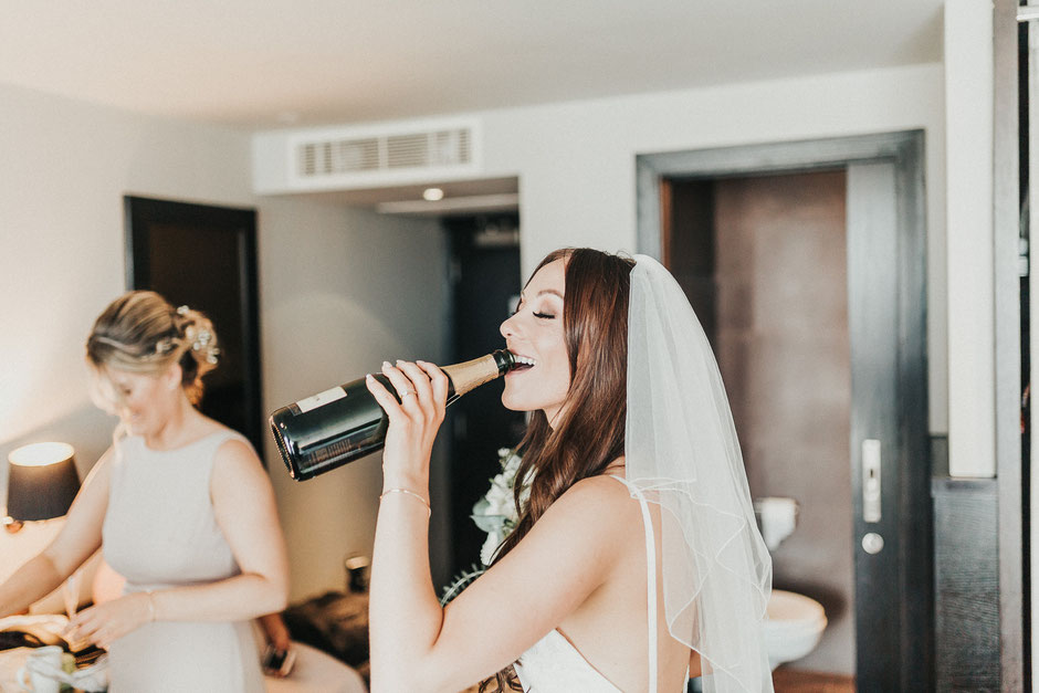 a bride in a veil drinking from a bottle of champagne