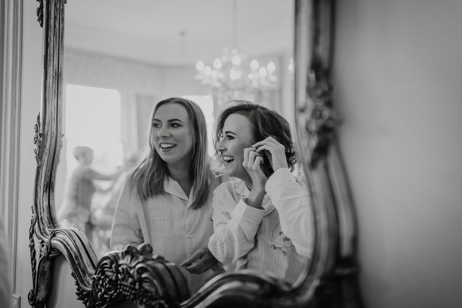 Sisters reflection in a mirror getting ready for a wedding